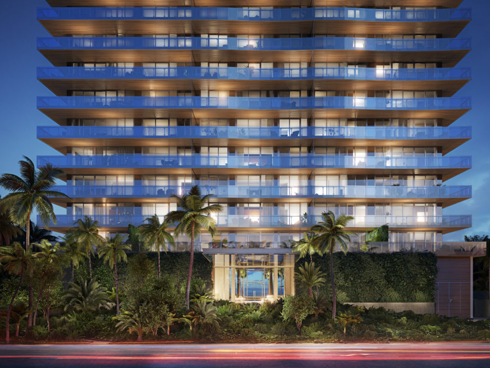 Exterior view of entrance to 57 Ocean condominiums in Miami. Has palm trees, a red sidewalk and lit balconies.