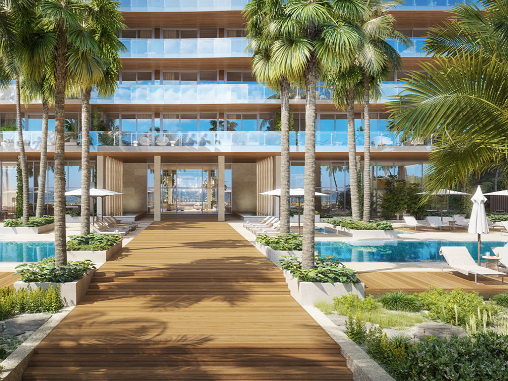 Exterior view of 57 Ocean condominiums outdoor pools and pathway in Miami. Has palm trees, brown pathway and two pools.