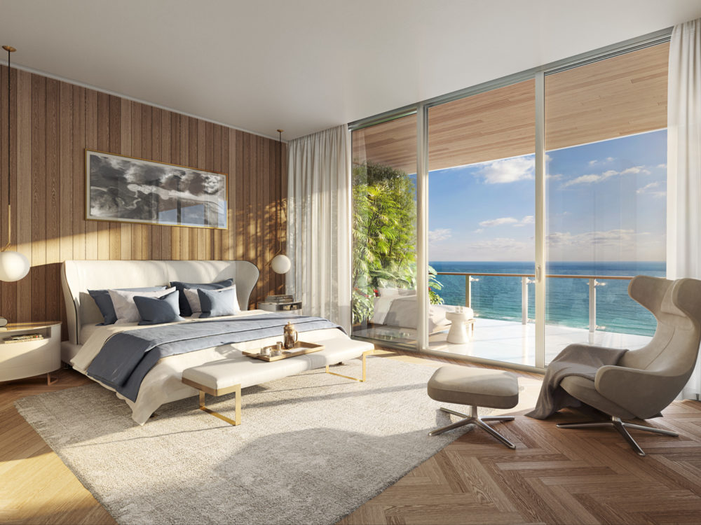 Interior view of 57 Ocean residence master bedroom with window view of oceanfront in Miami. Has wood floors and white walls.