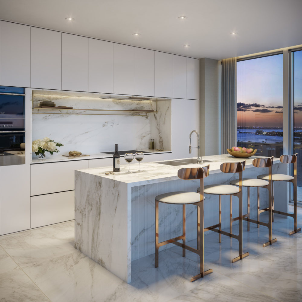 Interior view of 57 Ocean residence kitchen with window view of Miami. Has marble island countertop and white walls.