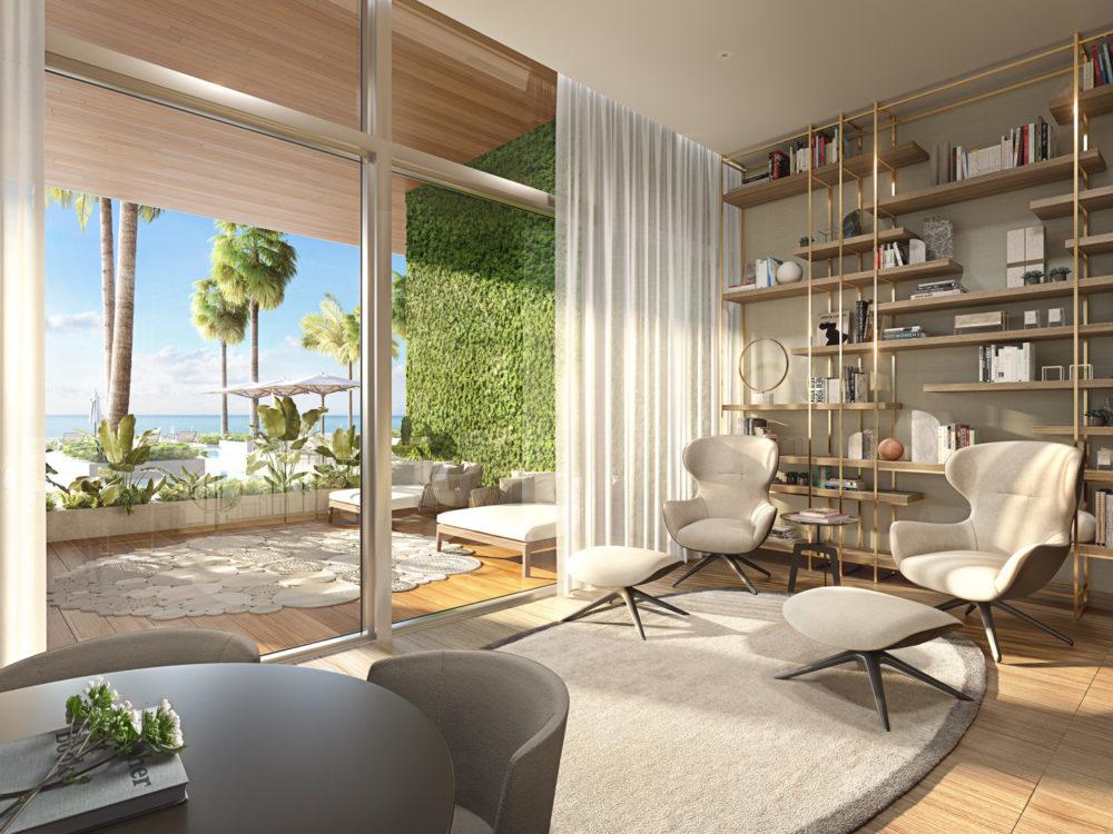 Interior view of 57 Ocean residence library and balcony with view of Miami. Has a bookshelf, longue chairs and glass windows.