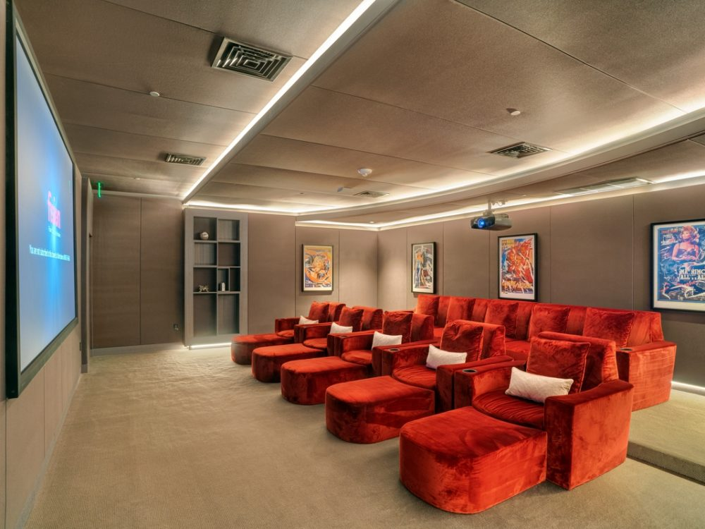 Interior view of Brickell Flatiron condominiums movie theater. Has large screen, red lounge chairs and glowing ceiling.
