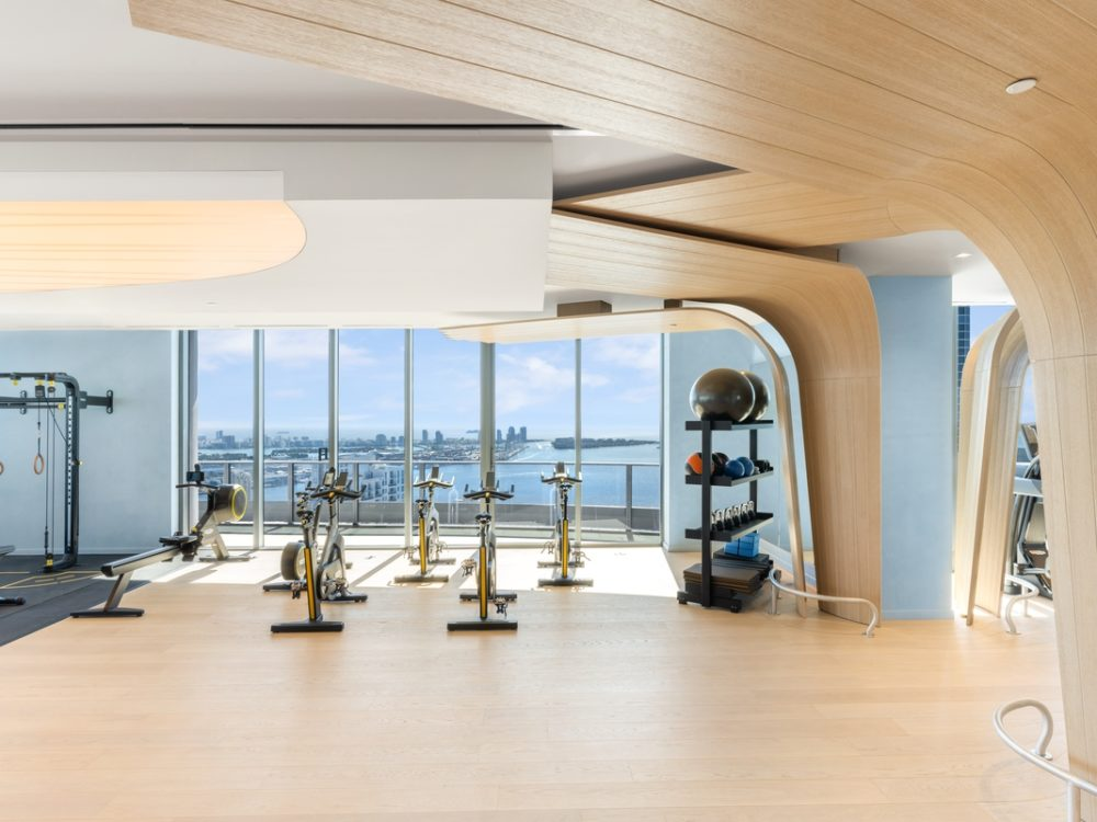 Interior view of Brickell Flatiron residence gym with oceanfront view. Has wooden walls and floors with workout equipment.