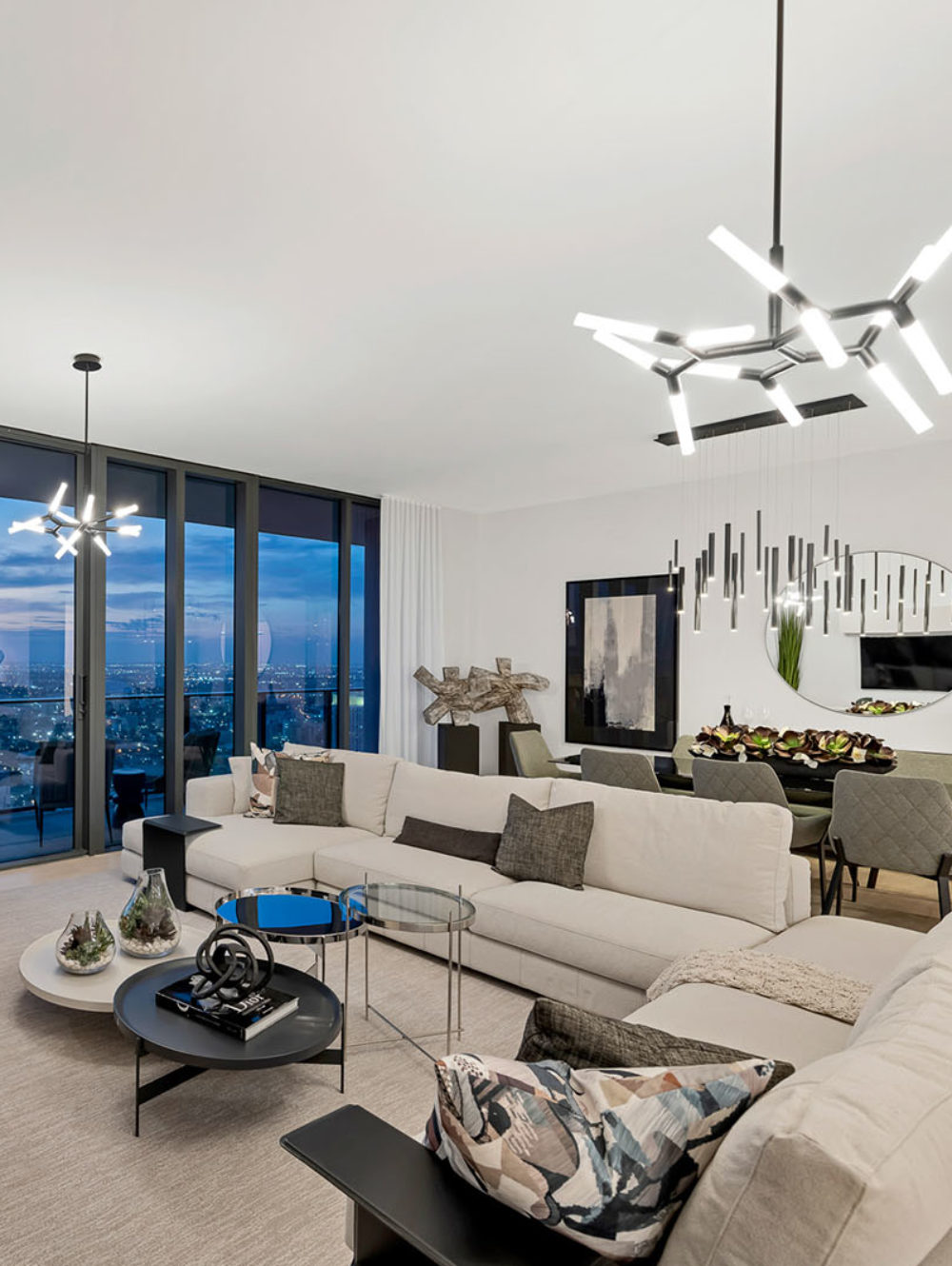 Interior view of Brickell Flatiron residence living room with window view of Biscayne Bay. Has beige couches and white walls.