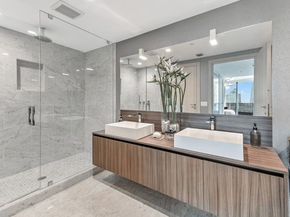 Interior view of Brickell Flatiron residence bathroom with view of Biscayne Bay. Has tile walls and floor with double sink.