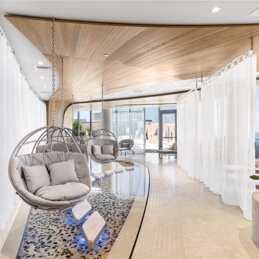 Interior view of Brickell Flatiron residence spa with view of Biscayne Bay. Has hanging seats, white curtains and wood wall.