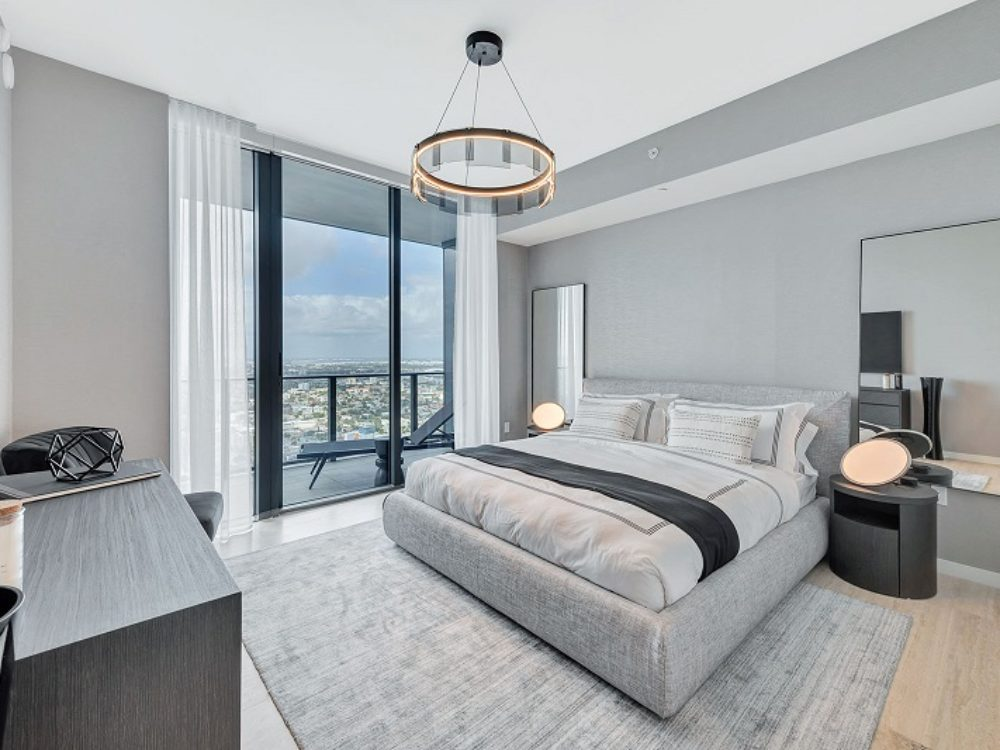 Interior view of Brickell Flatiron residence modern master bedroom with window view of Biscayne Bay and downtown Miami.