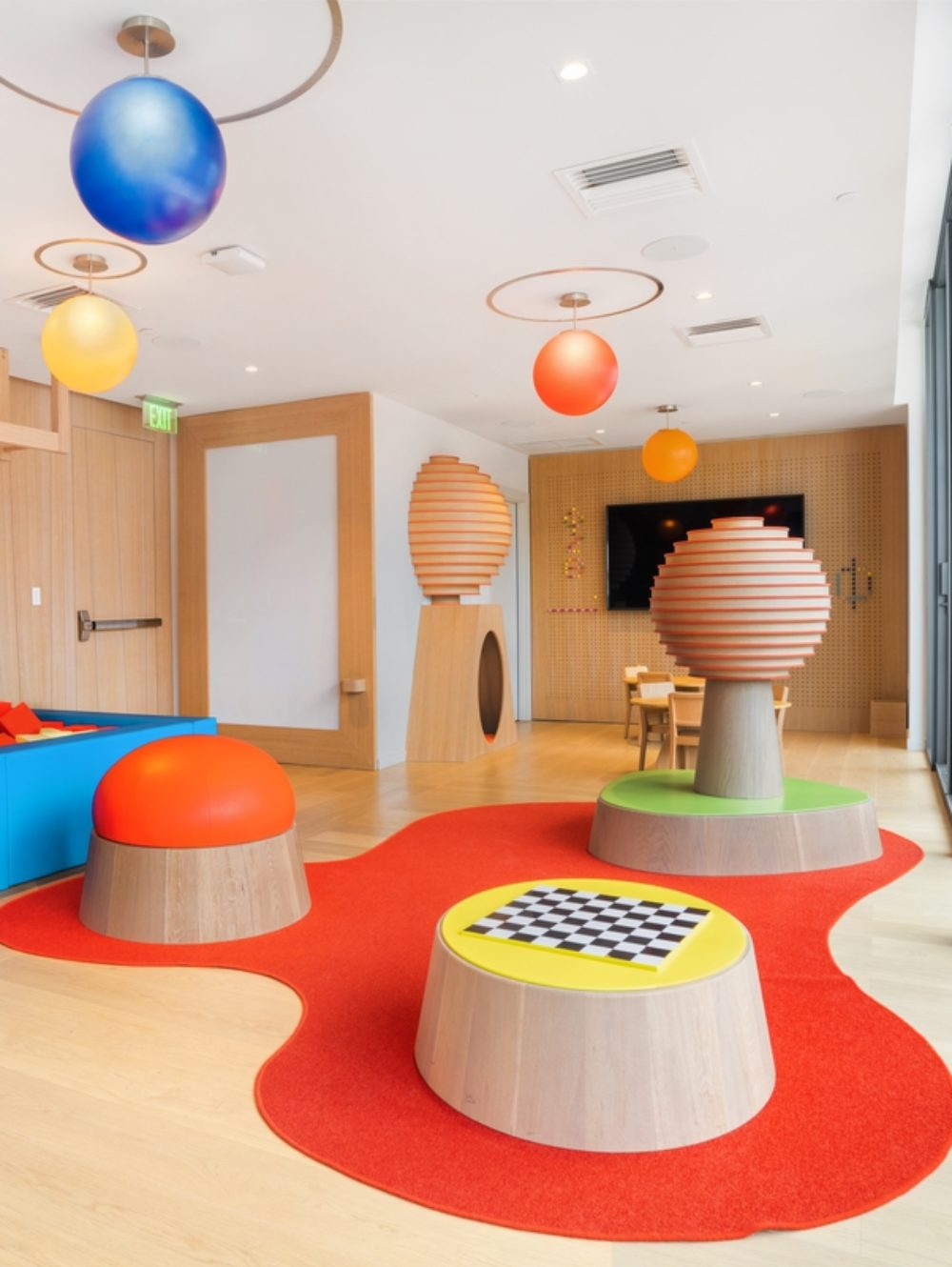 Interior view of Brickell Flatiron residence childrens playroom. Has a toy pit, checker board, and hanging solar system.