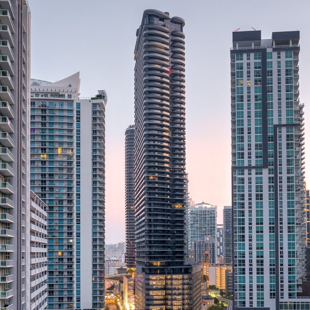 Exterior view of Brickell Flatiron condominiums with downtown Miami in the foreground. Has busy roads and tall buildings.