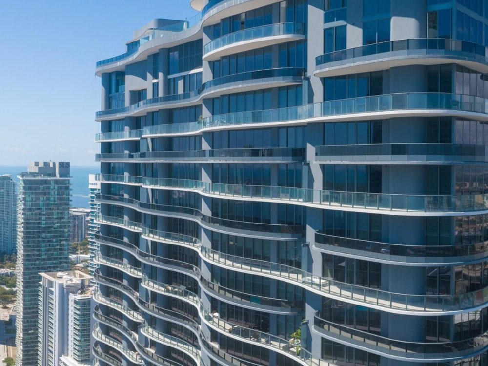 Exterior aerial view of Brickell Flatiron condominiums with downtown Miami in the background. Has Biscayne Bay view.