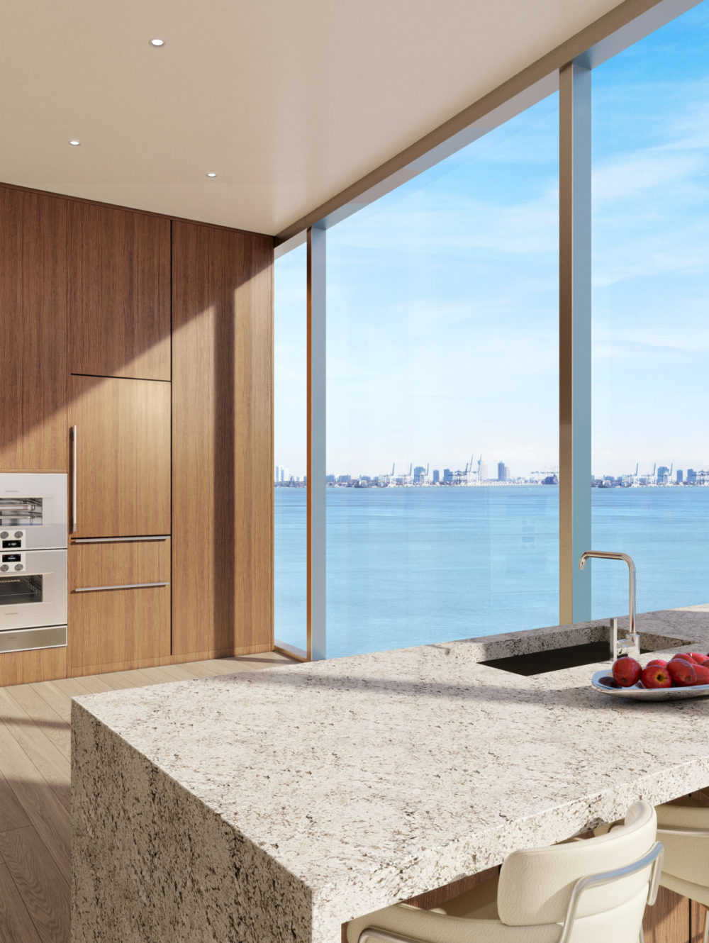 Kitchen with view at Una Residences in Miami. Open kitchen with large island, stone countertops, and wood built-in cabinets.