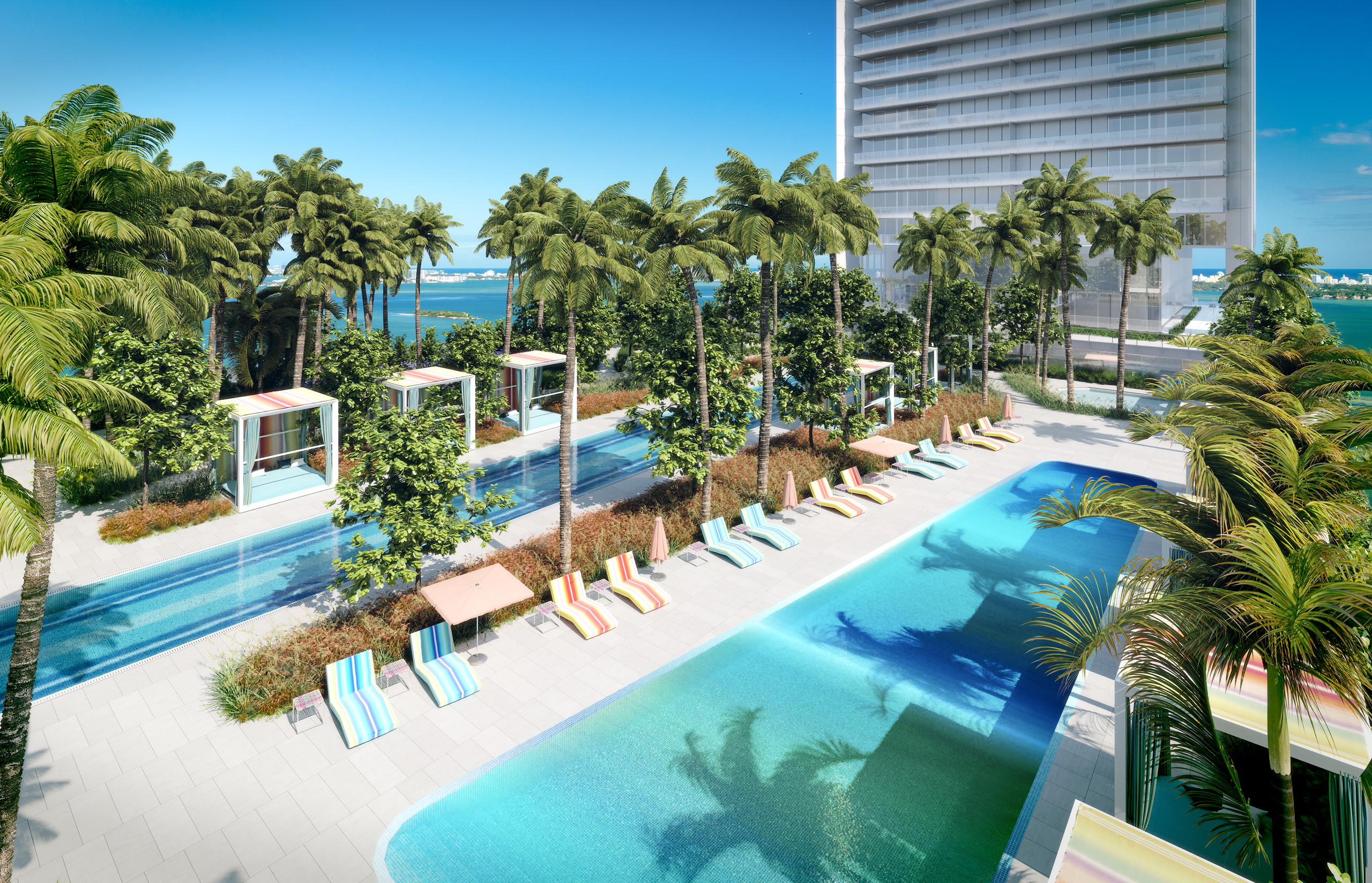 Exterior view of Missoni Baia residence outdoor pool deck with lounge chairs and palm trees. Overlooks the ocean in Miami.