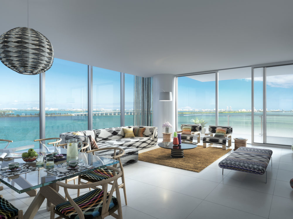 Interior view of Missoni Baia residence living room with oceanfront window view. Has glossy white floors and balcony.
