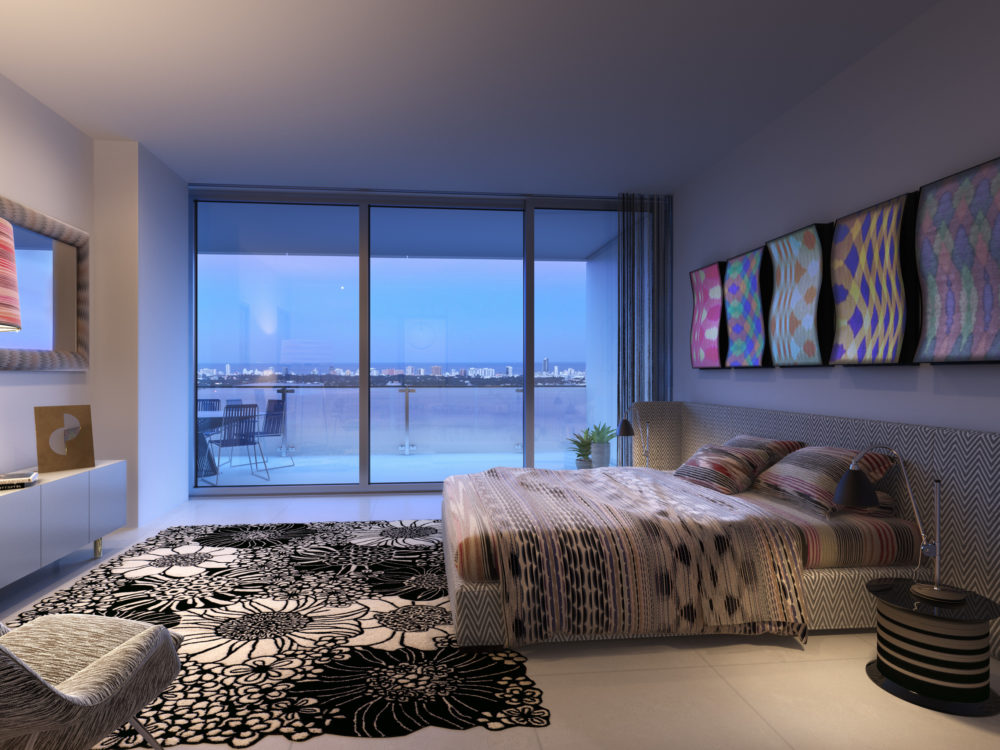 Interior view of Missoni Baia residence master bedroom with a balcony and oceanfront view in Miami.