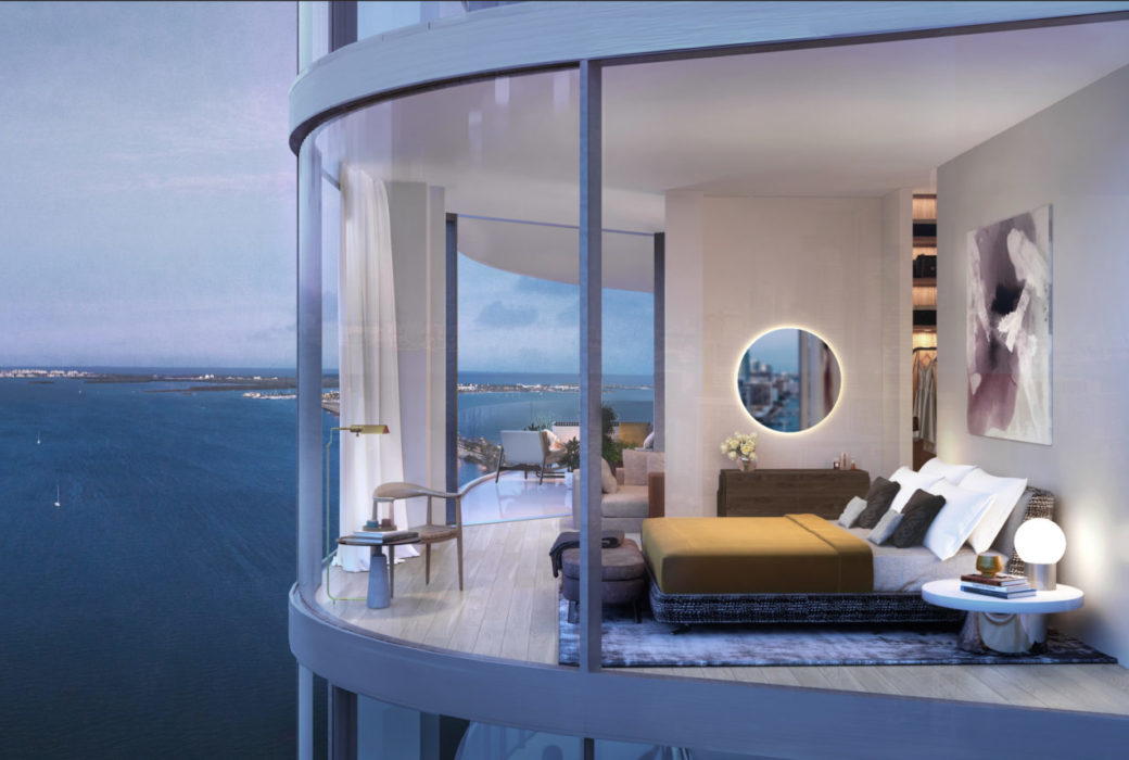 Exterior view of bedroom at Una Residences in Miami. A large bed, mirror & glass walls with attached bathroom and bay views.
