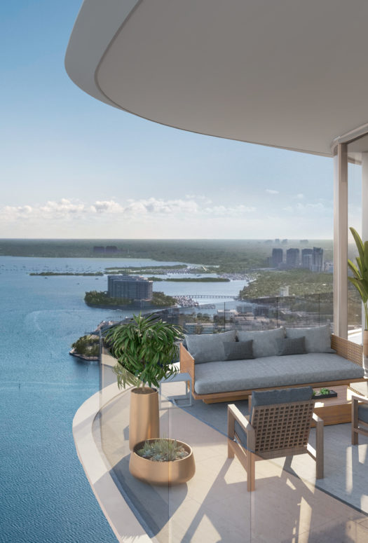 Exterior view of balcony overlooking the bay at Una Residences in Miami. Covered balcony with seating and potted plants.
