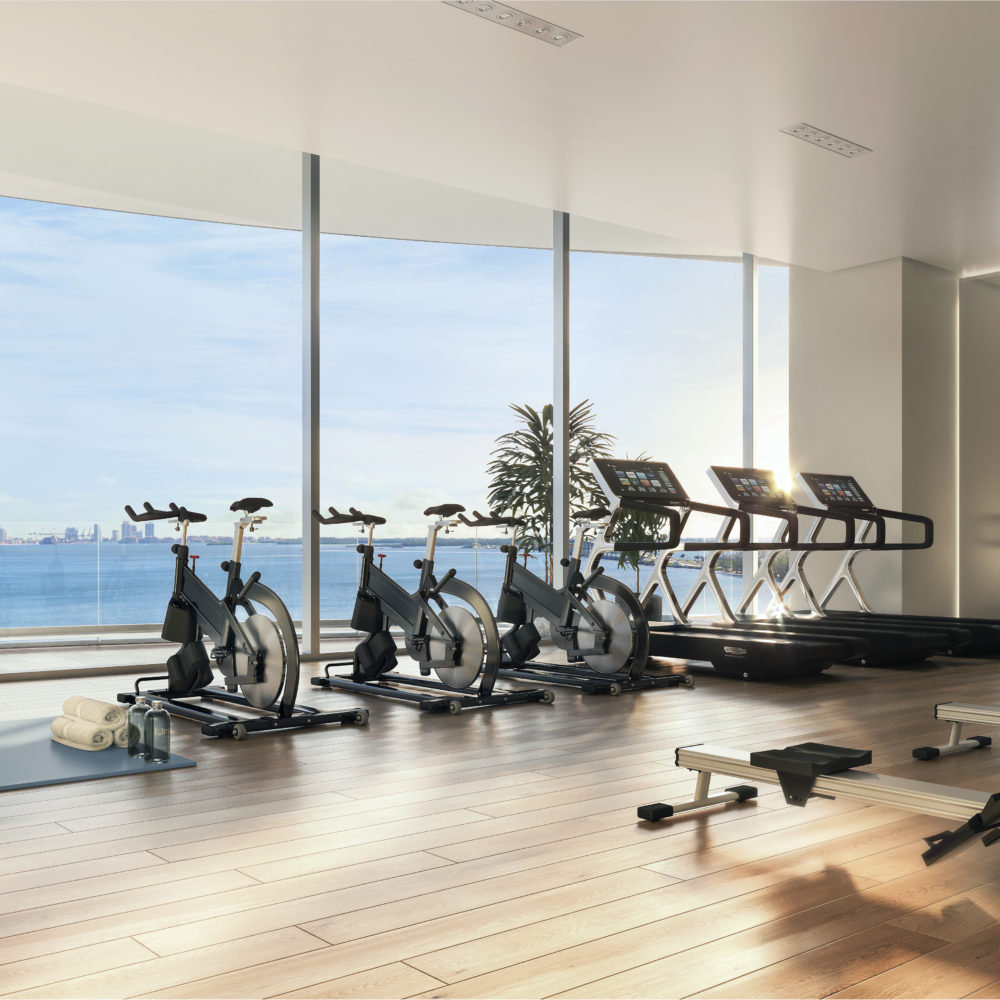 Workout room at Una Residences in Miami. Gym with exercise bikes, treadmills, a row machine, and yoga mats with a view.
