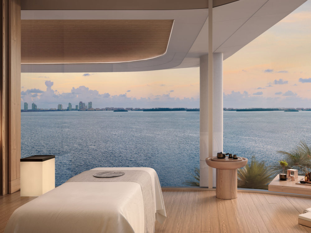 Una Residences spa room overlooking Biscayne Bay in Miami. Room with massage table, sitting area, large windows, and plants.
