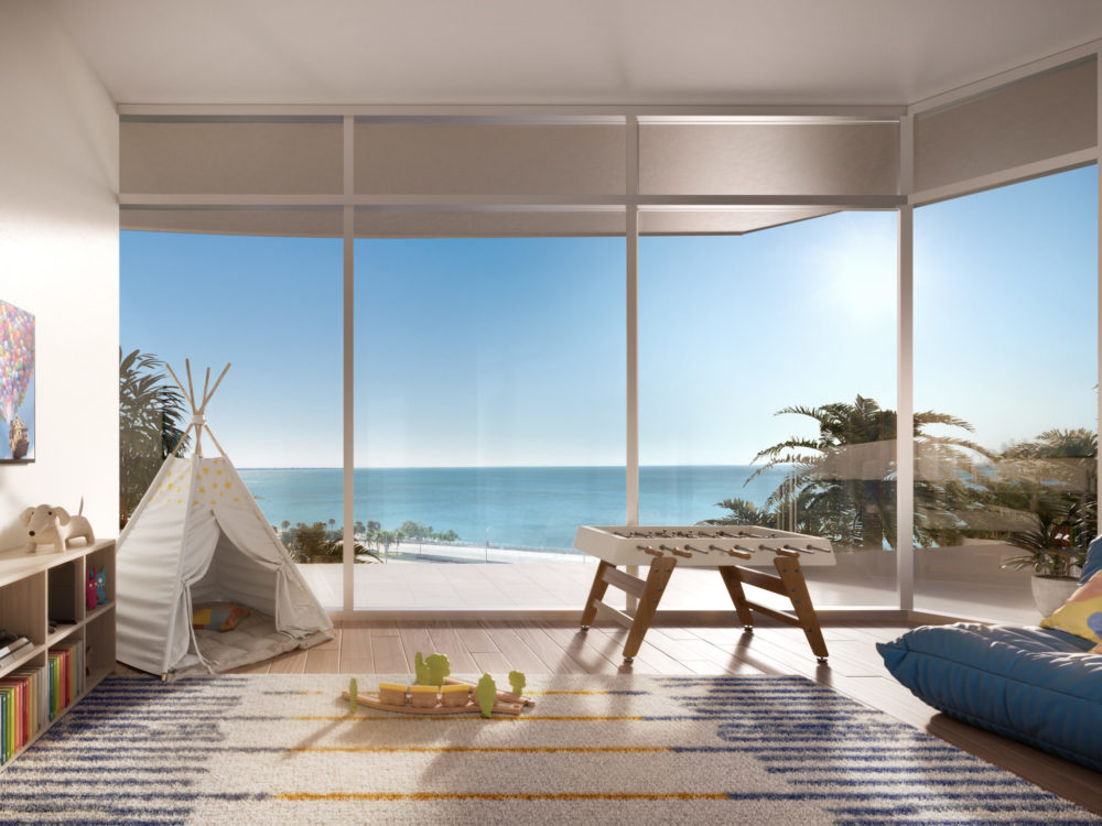 The kids playroom at Una Residences luxury condos in Miami. Playroom with a couch, toys, games, foosball table, and views.