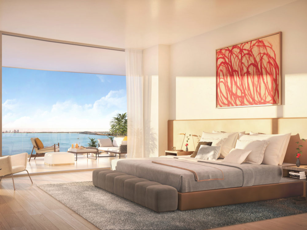 Bedroom with views of the marina at Una Residences in Miami. Large bed with painting on the wall, a chair, and large windows.