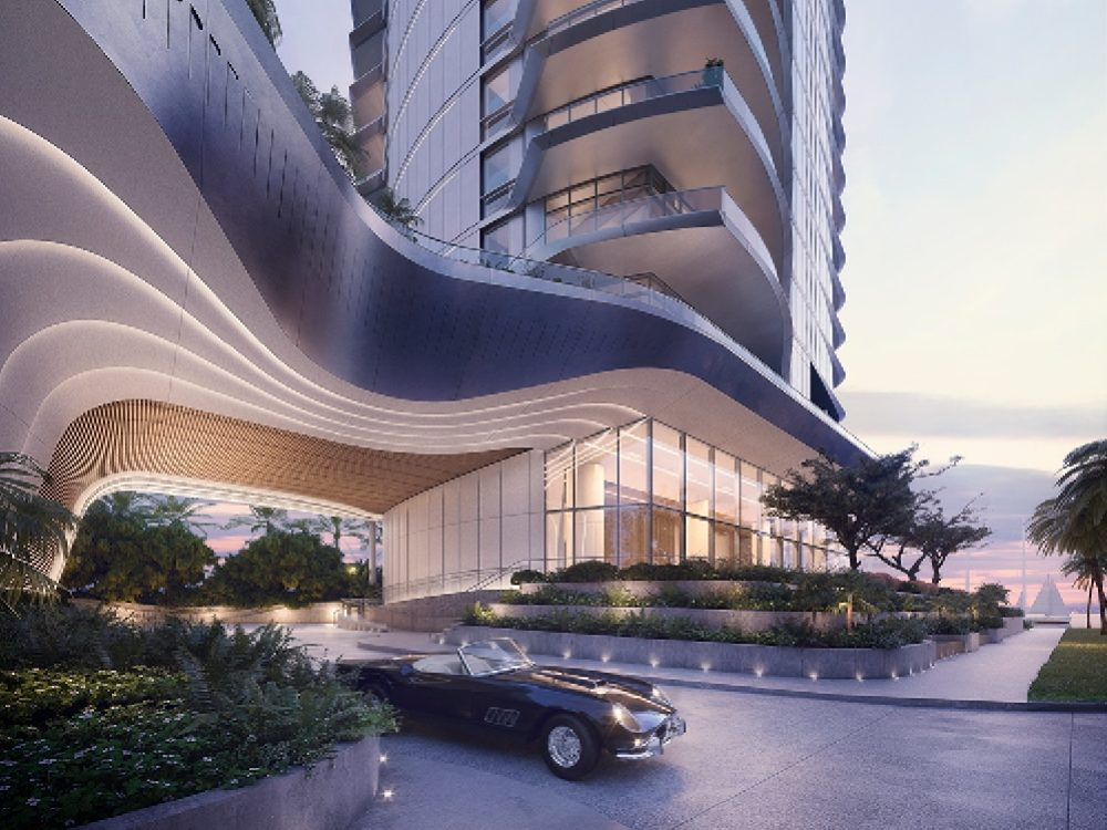 View of Una Residences driveway and front entrance in Miami. Ground view of high rise condo with a car in the driveway.