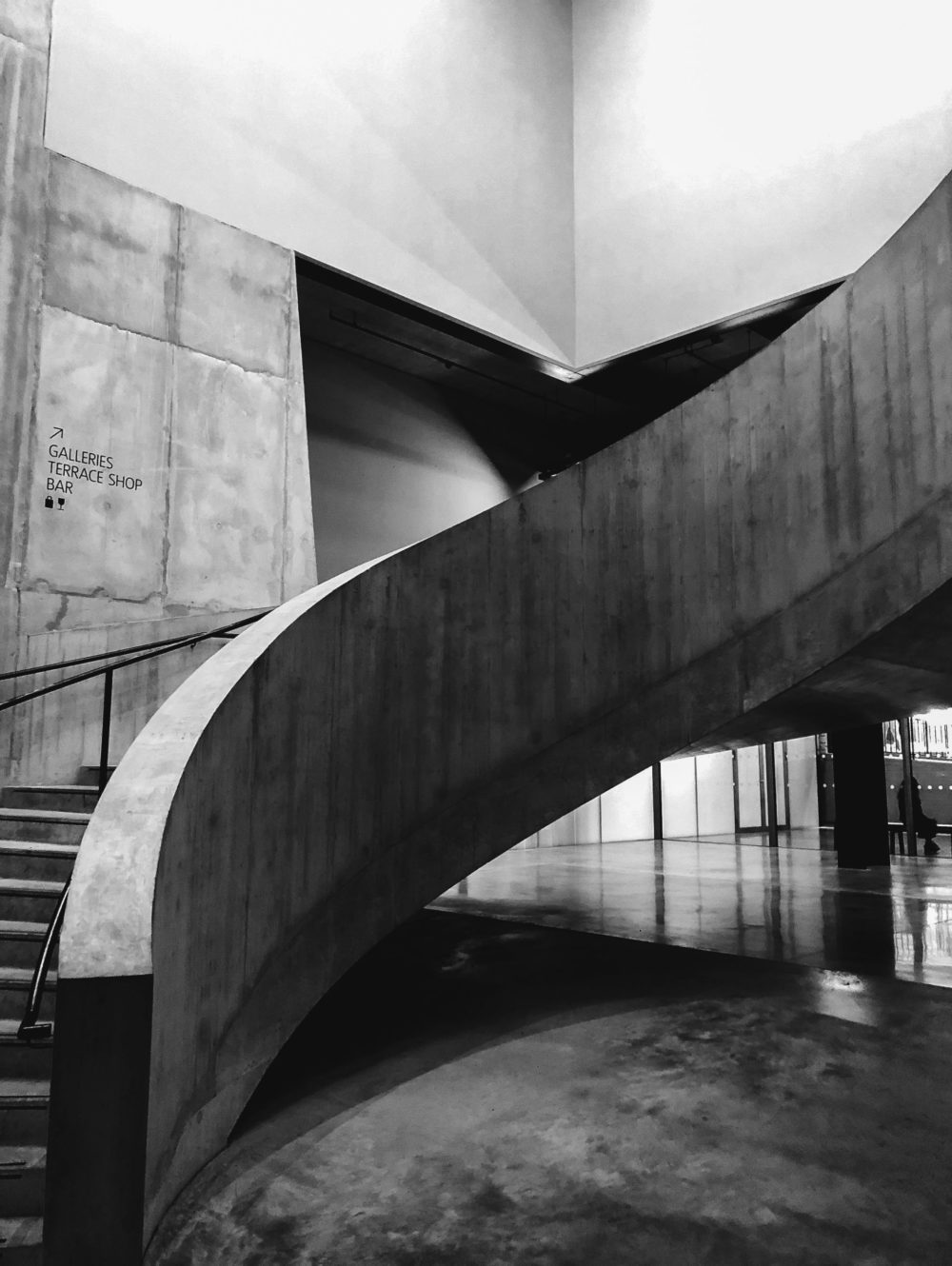 Black and white photo of curving staircase in building lobby. Stone floors and high ceiling with large windows in background.