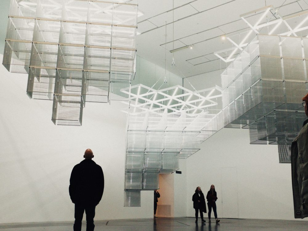 People walking through an art exhibit. Large open room with white walls and square structures hanging from the ceiling.