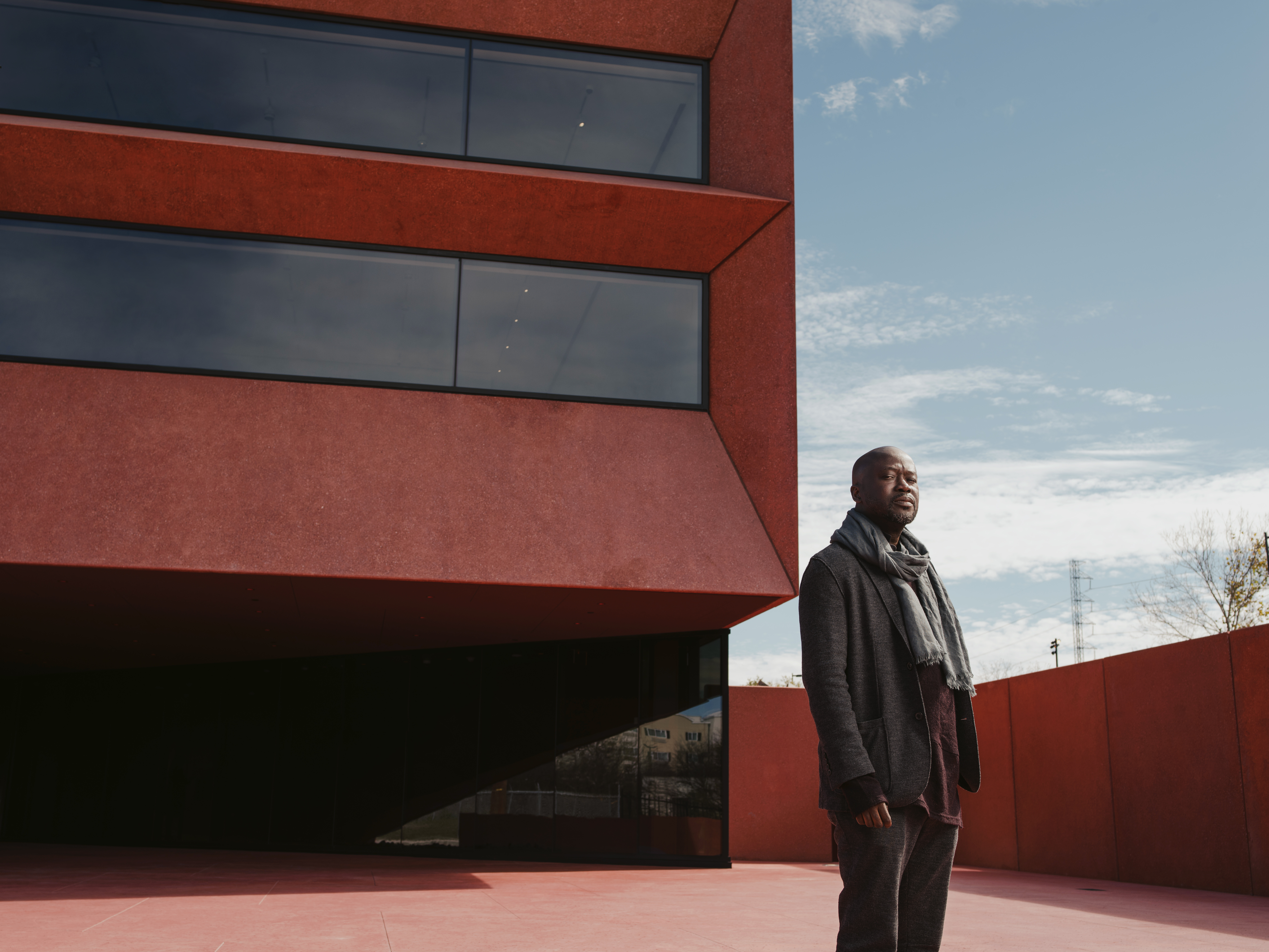 Sir David Adjaye standing outside of office building in jeans, a jacket and scarf. Picture taken by Josh Huskin.