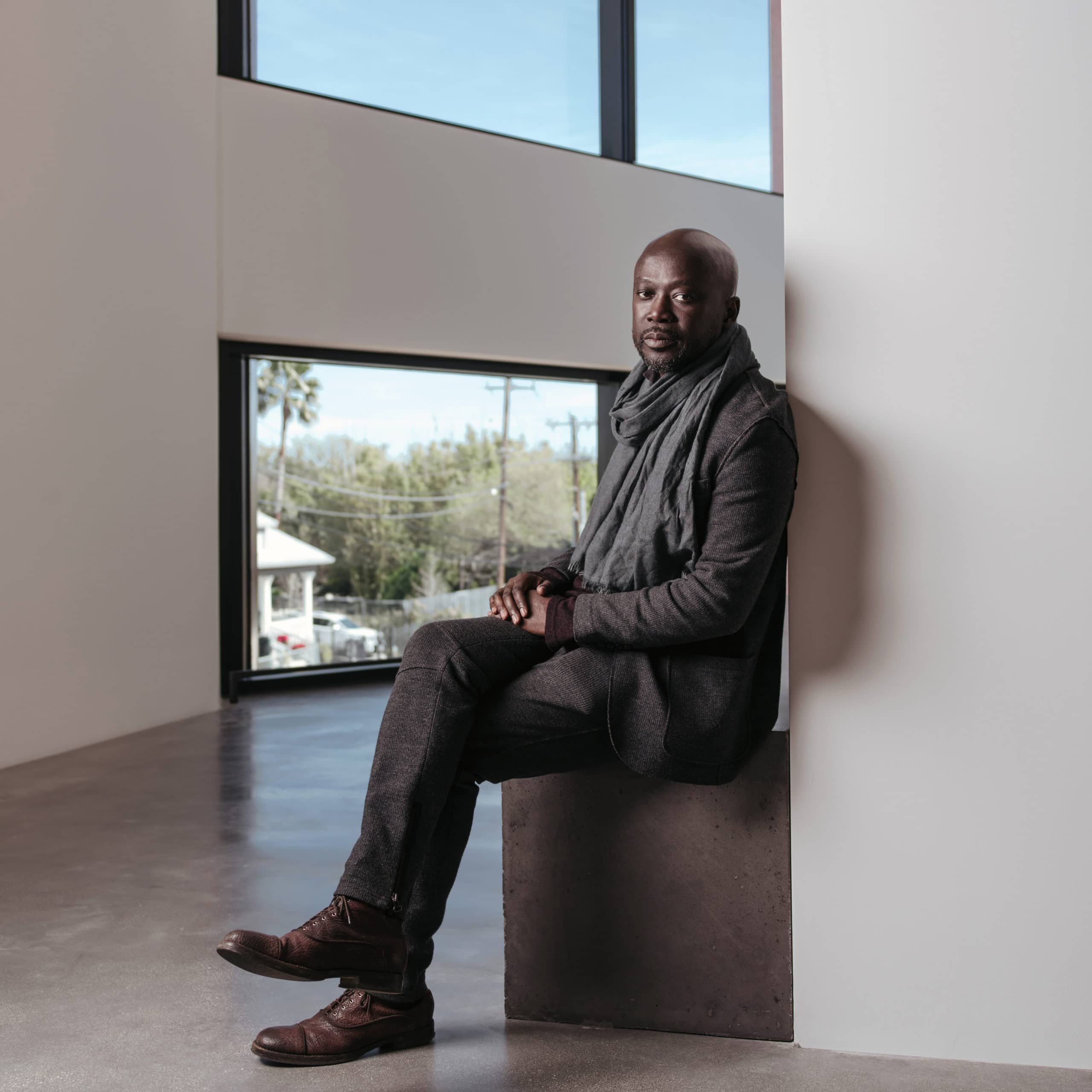 Profile picture of Sir David Adjaye by Josh Huskin. Man in jeans, jacket, and a scarf sitting with his legs crossed.