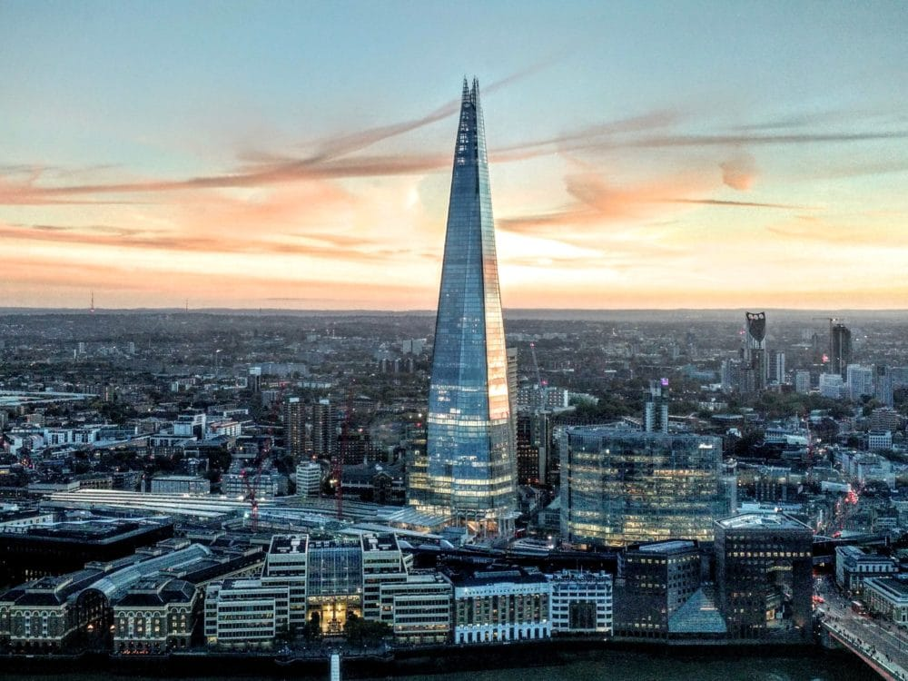 Aerial view of London, England with The Shard as the focal point. View of the city in the background during sunset.