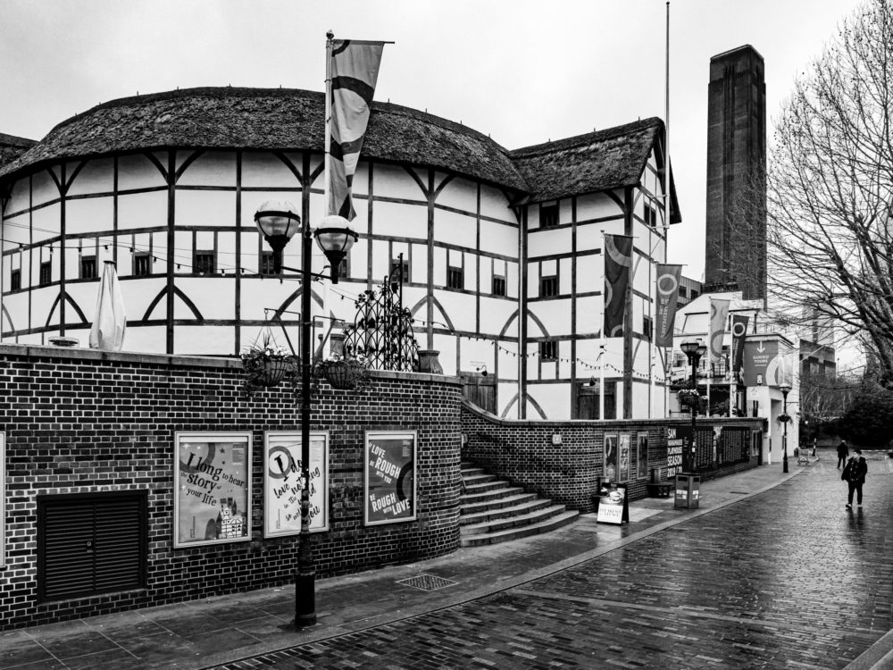 Black and white photo of brick sidewalk leading to Shakespeare's Globe Theatre. Brick walls and lamp posts with banners.