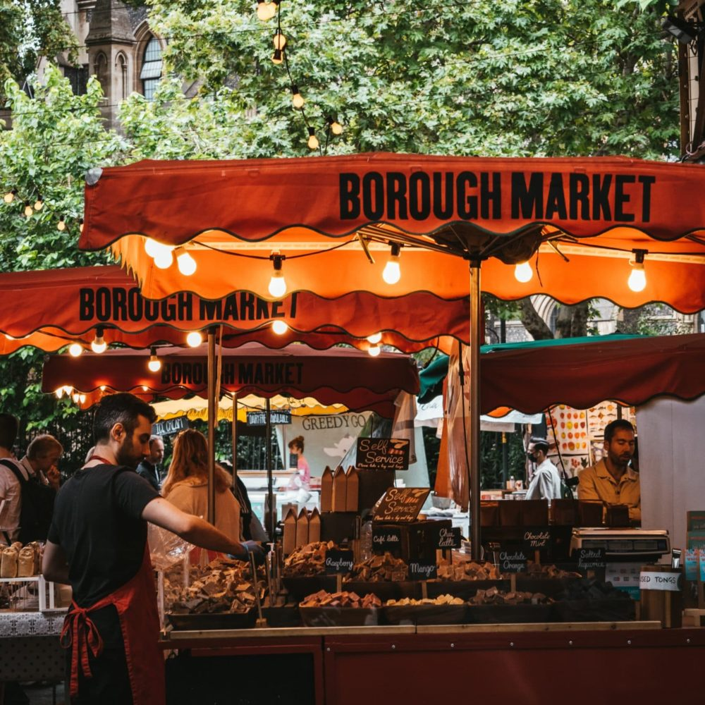 Vendors at London's Borough Market. Orange canopy's with lights covering vendors carts with people walking by.