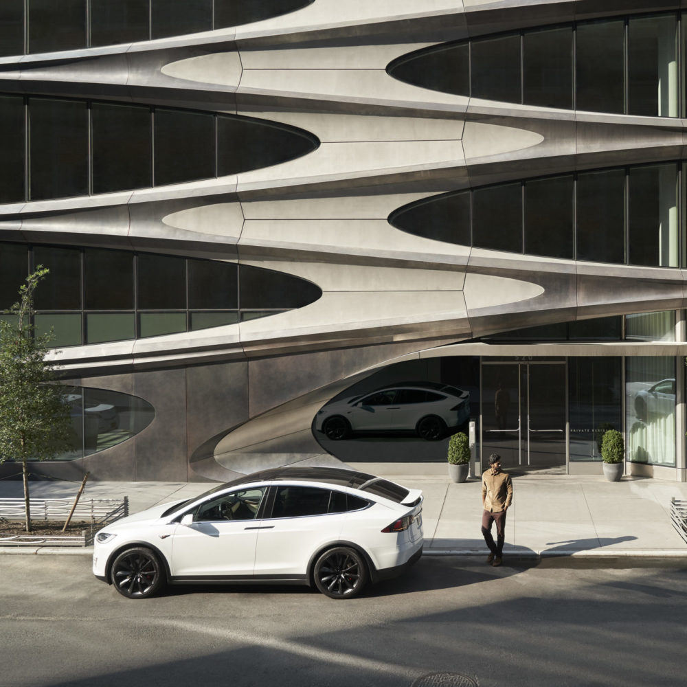 Detailed view of facade architecture of 520 W28 condominiums in NYC. Includes a view of a white car and person in the street.