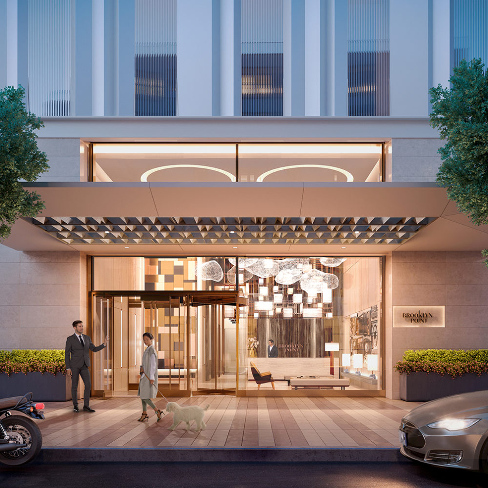 Exterior view of entrance to Brooklyn Point condominiums. Has a parked car and bike with people walking inside.