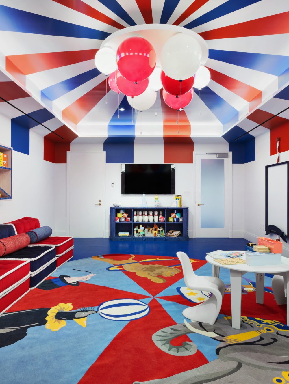 1010 Park Avenue NYC kids playroom with a colorful circus themed area includes activity boards and wall-mounted cubby.