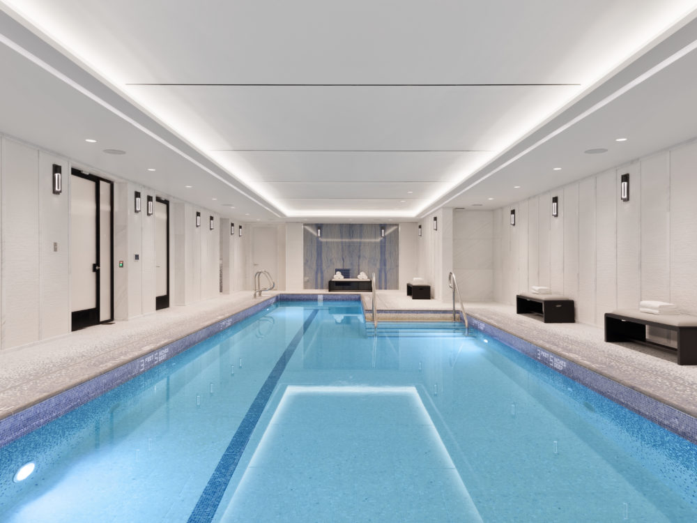 1010 Park Avenue private indoor pool includes stone-tumbled mosaic floor and walls paired with a marble feature wall in NYC.