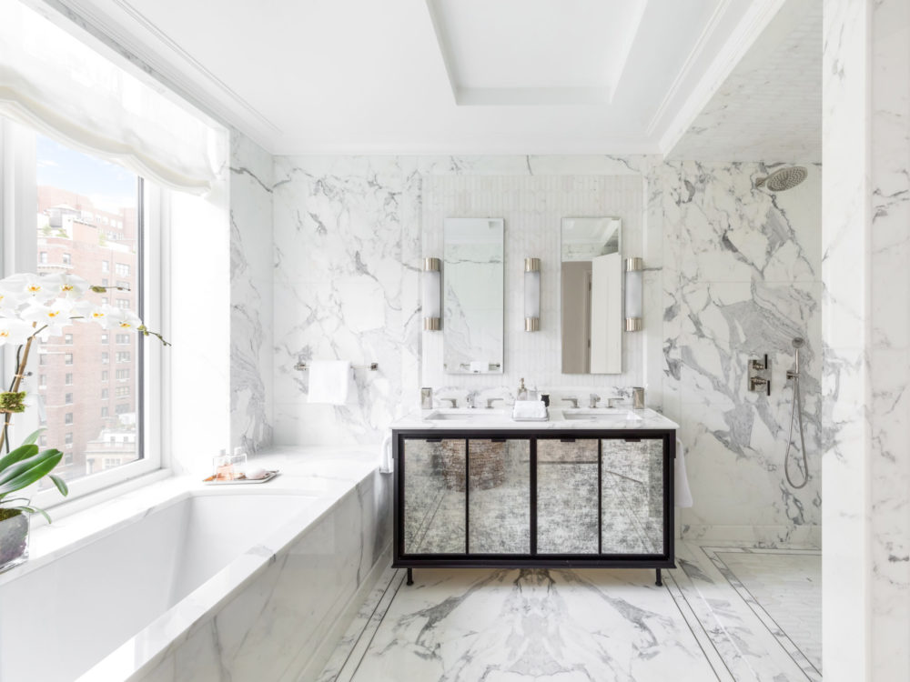 1010 Park Avenue master bathroom encased in statuary marble slabs with inset mosaic detail and a window view of NYC.