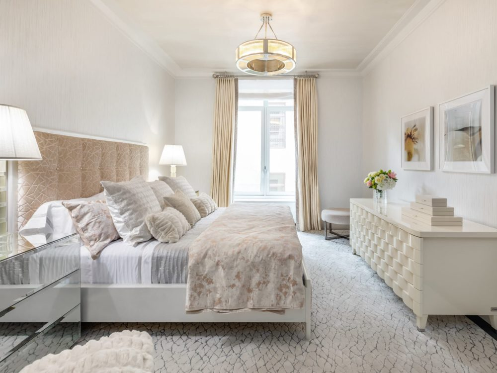 1010 Park Avenue master bedroom setup including white walls, ceiling and furniture with window view of NYC iconic park.