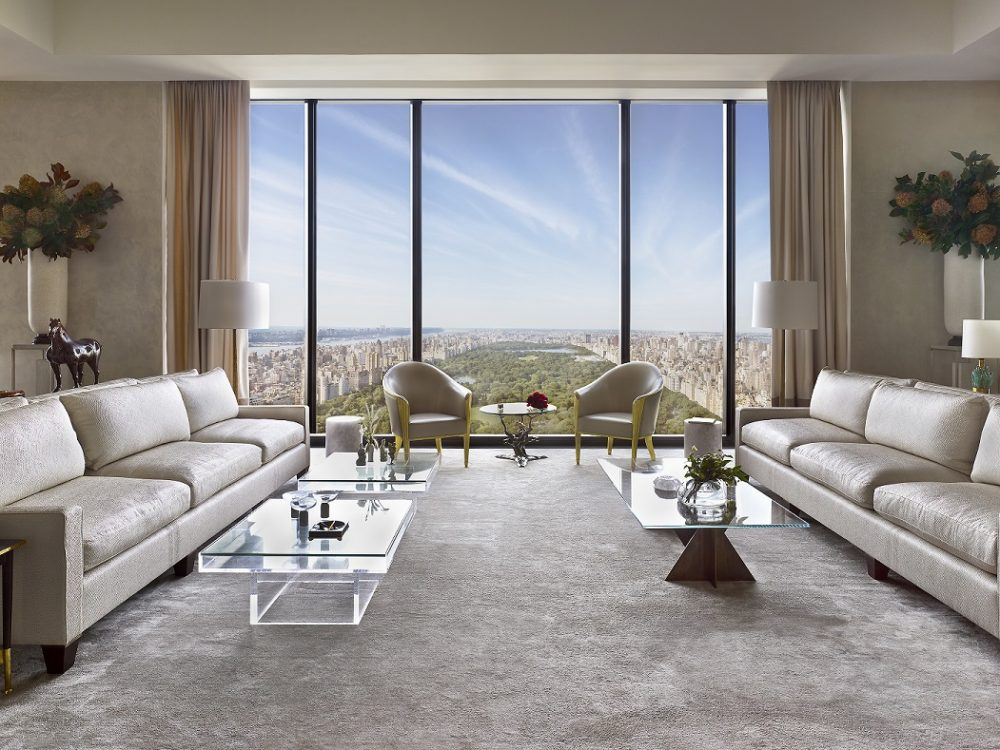 View of 111 West 57th street's condominiums great room with two beige couches, white walls and wide window overlooking NYC.