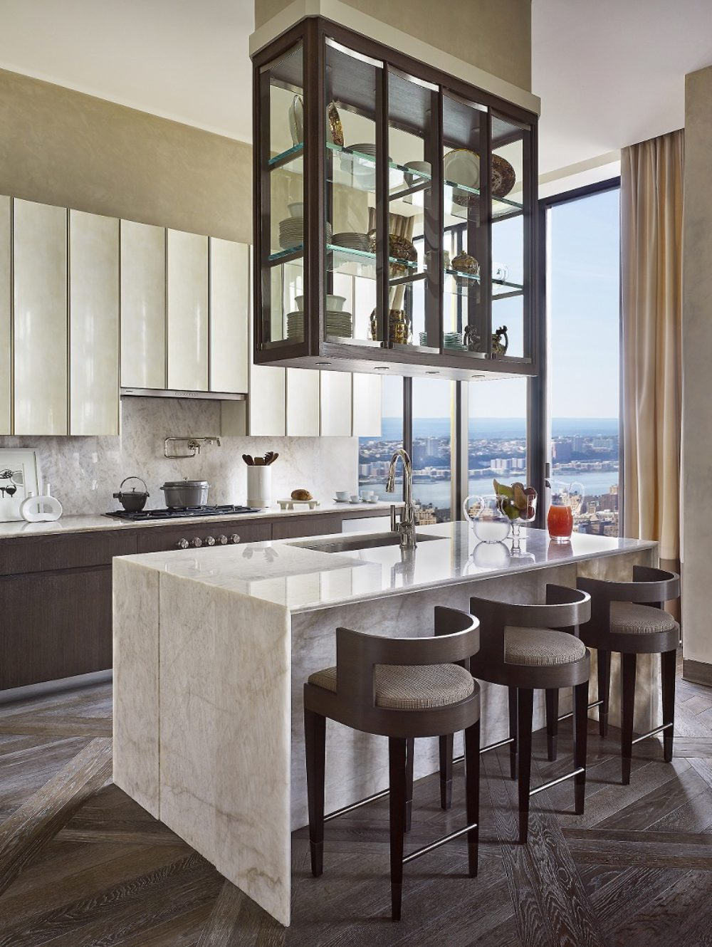 View of kitchen in 111 West 57th street condominiums with white table counters and black furniture with a window view of NYC.