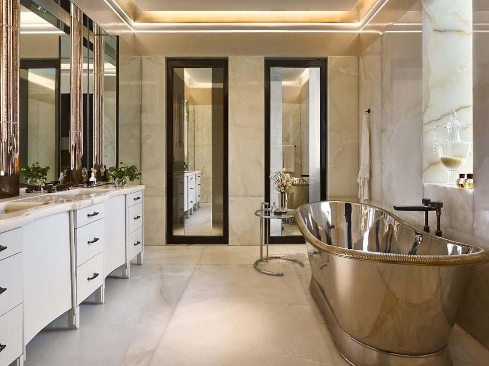 Full view of master bathroom with a golden tub and marble walls and floors inside 111 West 57th street condominiums in NYC.