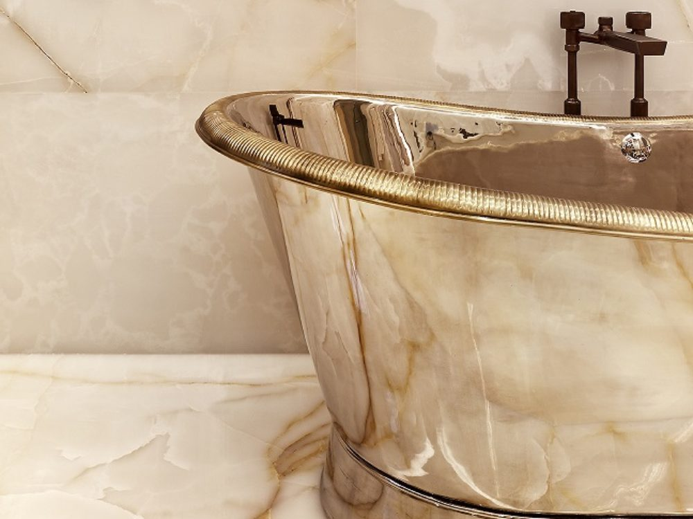 Master bathroom golden bathtub with marble walls and marble floor inside 111 West 57th street condominiums in New York City.
