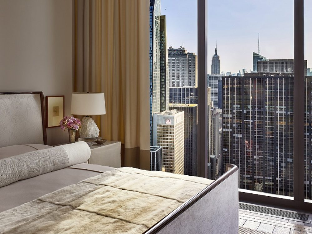 Interior view of 111 West 57th street condominiums master bedroom with white walls and a window view of New York City.
