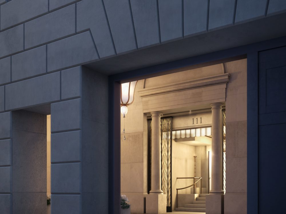 Exterior view of a porte cochere entrance to 111 West 57th street with white designed walls and night lamps in New York City.