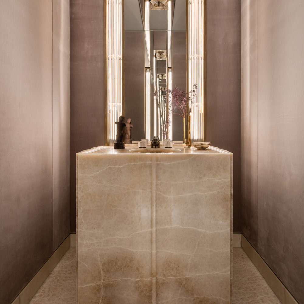 View of powder room in 111 West 57th street condominiums with beige marble counters and white walls in New York City.