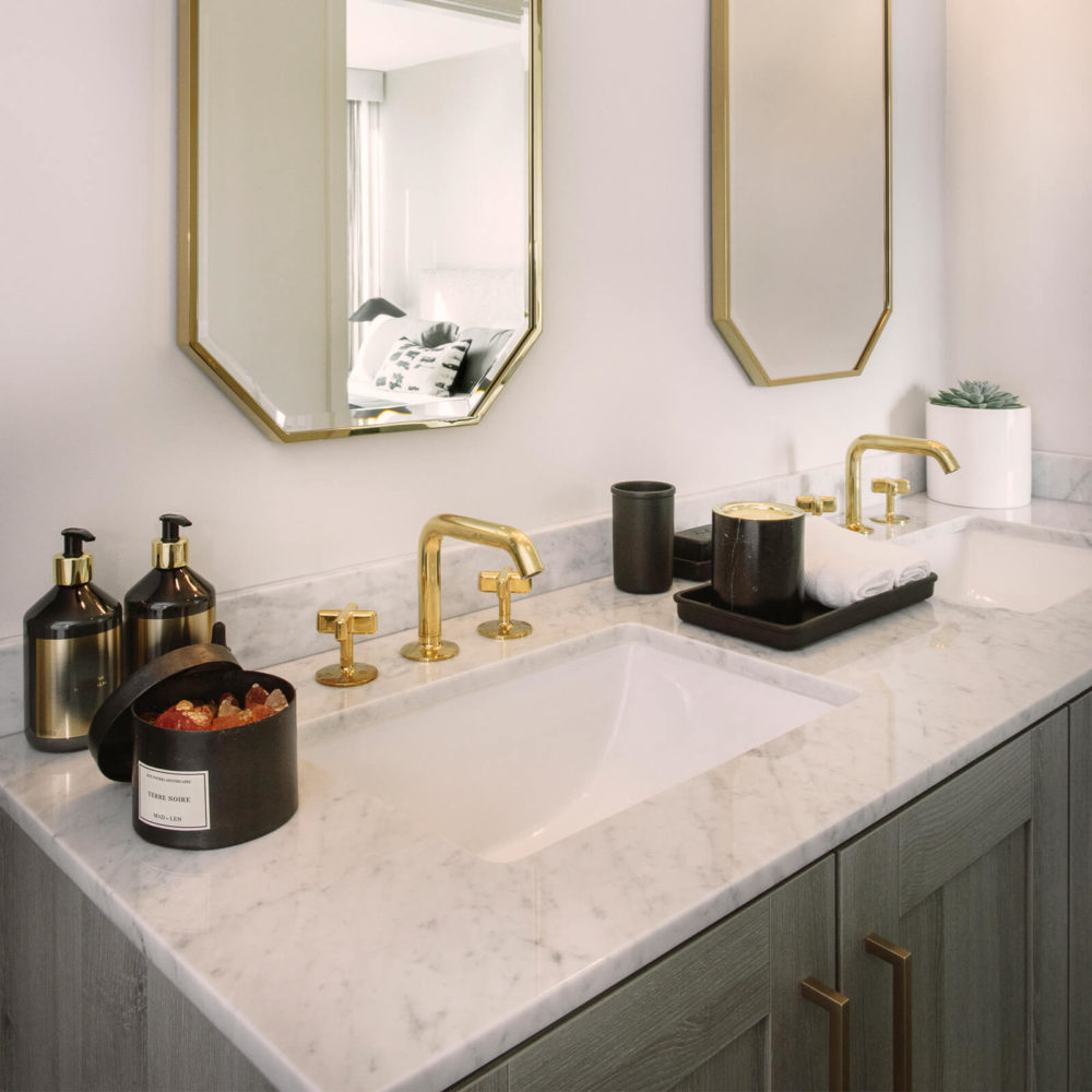 Bathroom in The Harrison condominiums in San Francisco. Double vanity with stone countertop and two mirrors on the wall.