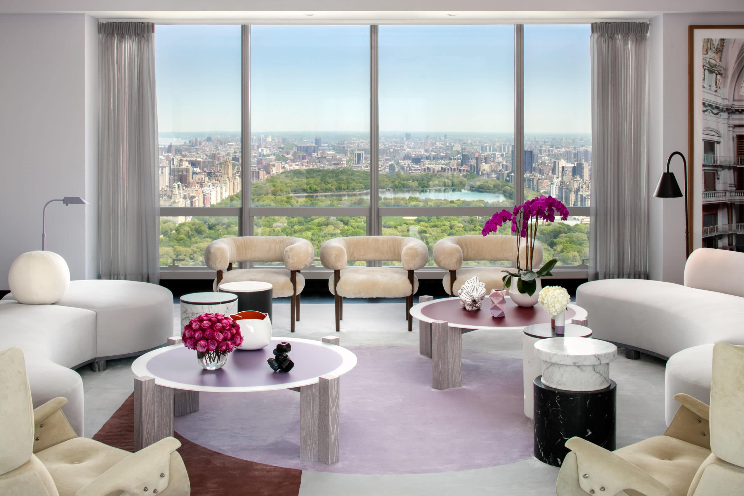 Living room at One 57 condominiums in New York. Light colored furniture, two coffee tables and floor-to-ceilings windows.