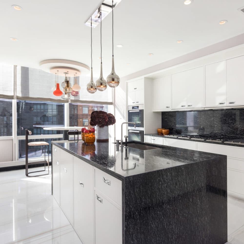 Kitchen at One 57 luxury condos in NYC. White cabinets, walls and island with black marble countertop with small table.