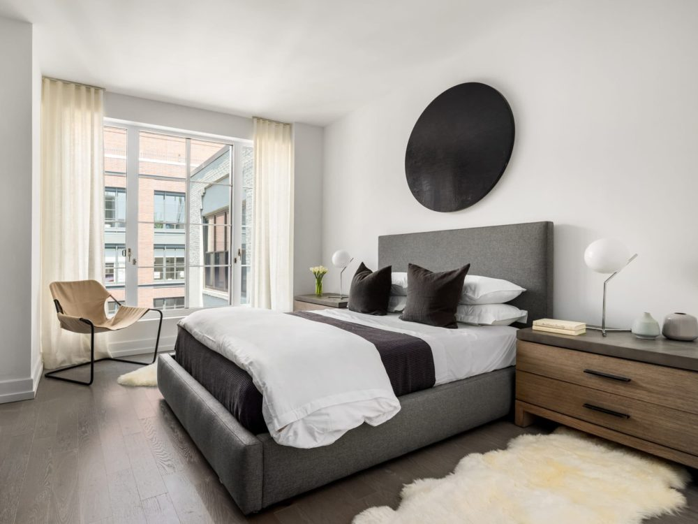 Interior view of 70 Charlton residence bedroom with window view of New York City. Has wood floors, white walls and dark bed.