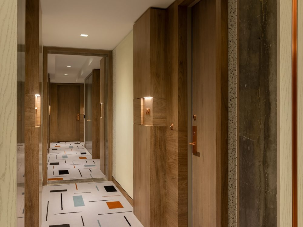 Interior view of Brooklyn Point condominiums hallway. Has patterned floors, beige walls and wooden door frames.